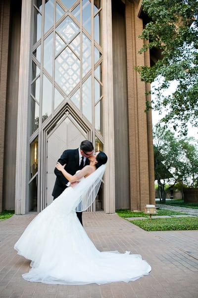 Bride and groom kissing dramatically with a kiss in front of the Marty Leonard Chapel in Fort Worth, Texas on their wedding day.