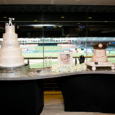 bride and groom cakes displayed on table with the baseball field in the background