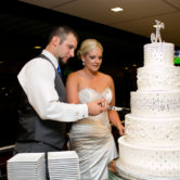 cute bride and groom cutting the five tier wedding cake with rhinestones