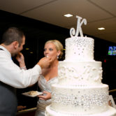 awesome bride and groom eating the wedding cake together