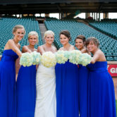 beautiful bride and bridesmaids pointing their wedding bouquets at the camera for a group photo