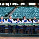 group photo of the groomsmen and groom in the dugout of the texas rangers baseball players