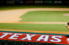 Dallas wedding photographer captured bride and groom kissing on top of Texas Rangers dugout at ballpark wedding.