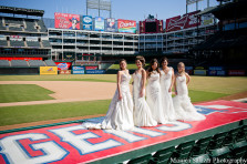 Brides standing on top of dugout at Texas Rangers Baseball Ballpark, Globe Life Park for Texas Rangers bridal show and weddings.
