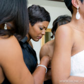 Tamron Hall helps her friend and bride Connie put on her beaded lace wedding dress