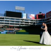 bride and groom on baseball field during wedding photos at texas rangers baseball field
