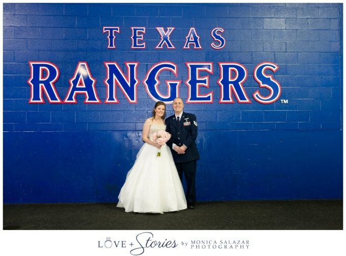 texas rangers baseball ballpark wedding with bride and groom portrait in front of the blue rangers wall in the dugout area of the stadium