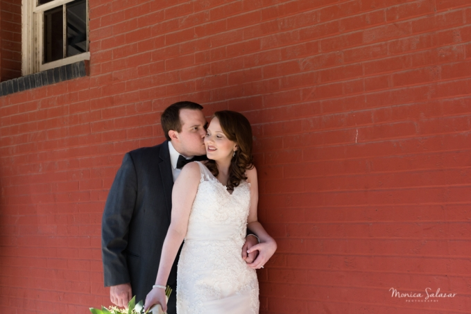 Bride and groom pose in front of red brick wall before the wedding ceremony at the Grand Hotel in McKinney.