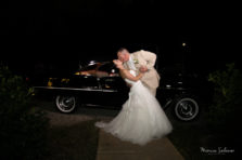 Bride and groom kiss in front of vintage car at the end of the night on their wedding day. Wedding was at The Orchard wedding venue in Azle, TX.