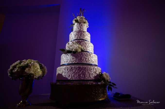 Dallas museum of art wedding cake with blue uplight and floral decorating the cake and table photos by Dallas wedding photographer Monica Salazar.
