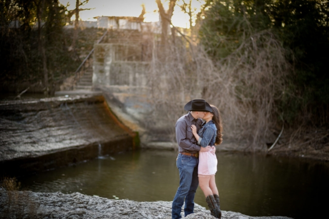 Fort Worth engagement session photos by Fort Worth wedding photographer of Adrianna and Sean at a park with a waterfall, sunset and open fields. Engagement session with a rustic and modern style.